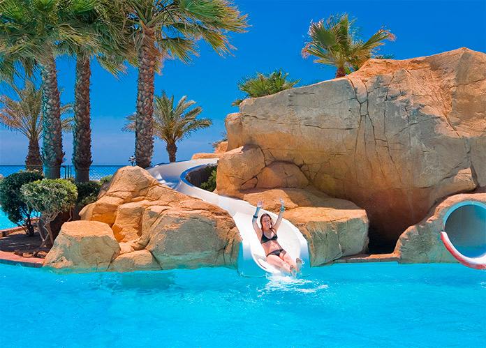 Mujer disfrutando de uno de los toboganes de la piscina de Playaluna Hotel