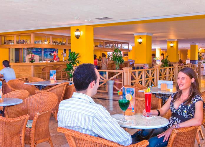 Pareja disfrutando de un refrigerio en la cafetería del Playaluna Hotel